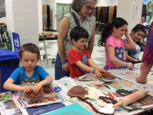 Young students sit around a table kneading clay into bowl-like shapes. Some adults look on.