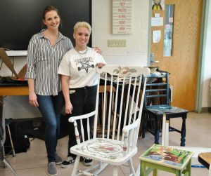 Student and teacher pose together by a painted rocking chair.