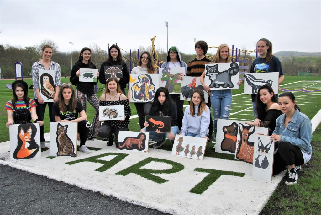 Group photo of students holding their paintings of animals outside.