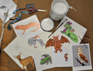 Drawings, illustrations of animals spread out on a table surrounded by art supplies
