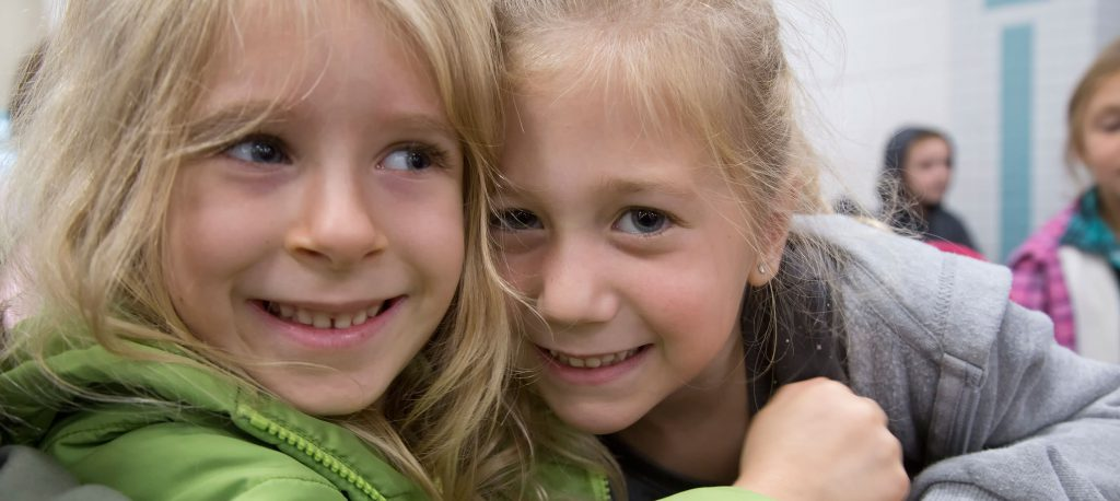 Two kindergarten girls hug one another and smile