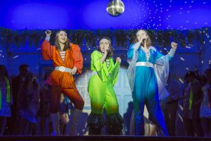 Three singers dressed in 70s pop stage costumes