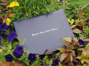 Diploma cover with district name imprinted laying on grass, flowers.