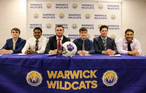 Six high school students wearing suits and ties sit at a table that is covered with a purple banner with gold writing. The banner says Warwick Wildcats.