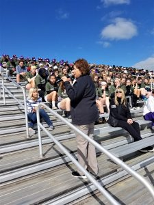 Students sitting on bleachers. Woman addressing students.