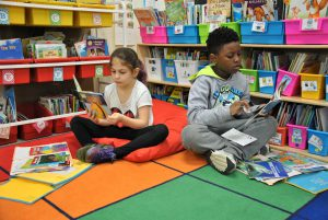 Two students sitting on a classroom rugs select books stacked in bins in their classroom library.s