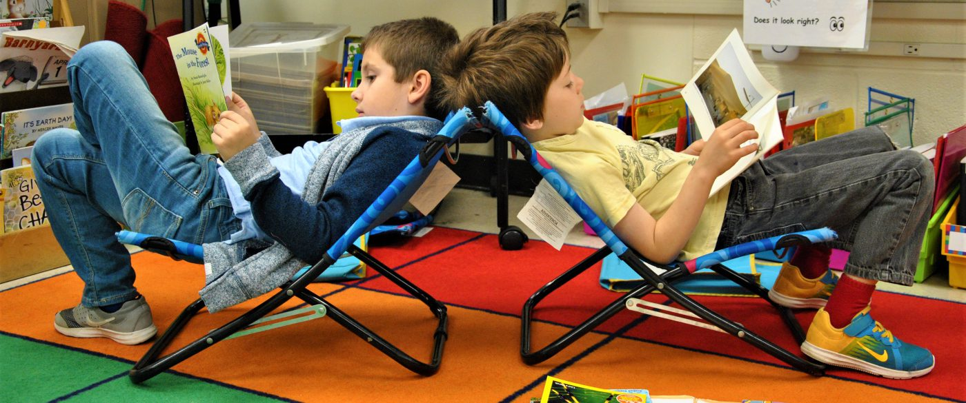 Two students sit on beach chairs, back to back, reading picture books.