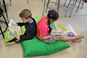 Two students sit back to bac on a large people reading picture books