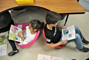 Two students sit back to back in scoop chairs reading picture books.