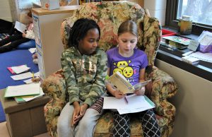 Two students sharing a book and a chair.