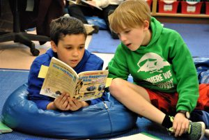Two students sitting on bean bags share a book.