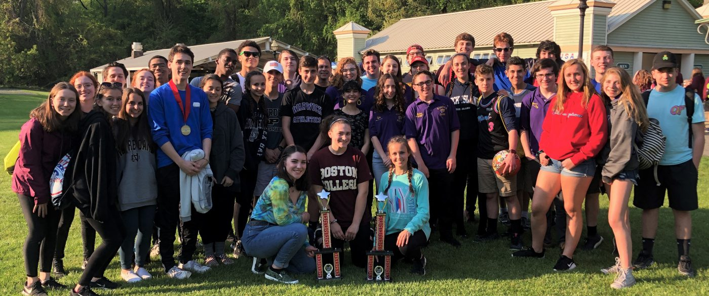Group photo of high school bands who won 1st place trophies at Music In The Parks festival. They are standing on a green lawn with trees and small buildings in the background. Their two trophies are in the foreground.