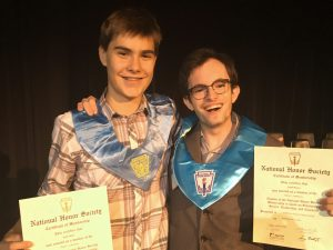 two male high school students hold their NHS certificates