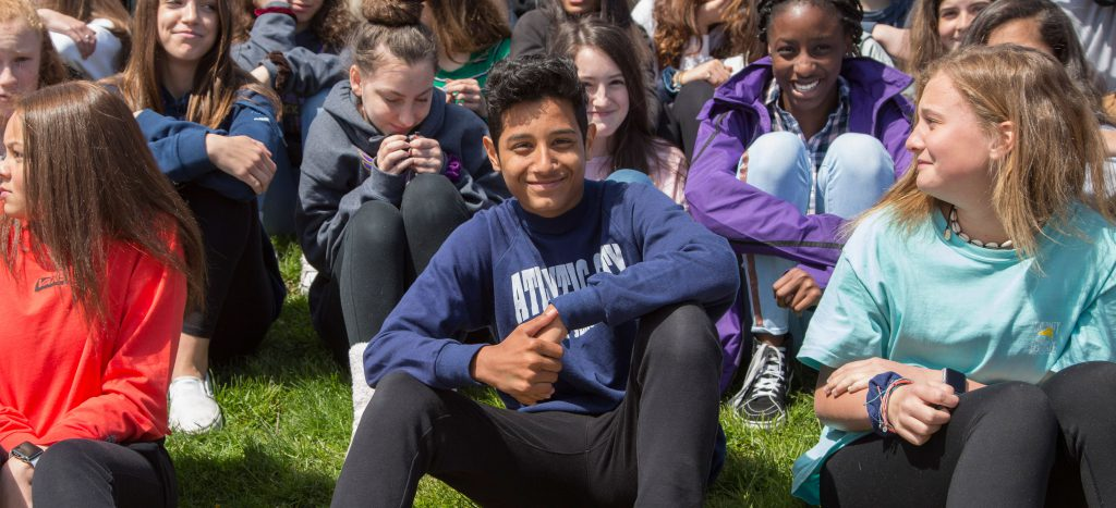A large group of grade 8 students sitting on the grass in the sunshine