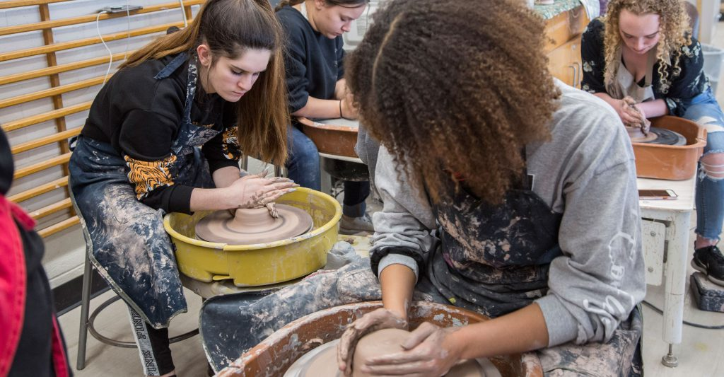 three students work on a potter wheel