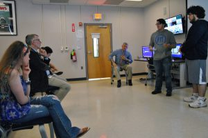 Two students present to a group of students and a guest.
