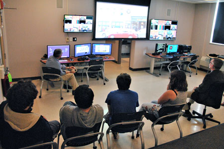 A group of people watch a video on a TV screen.