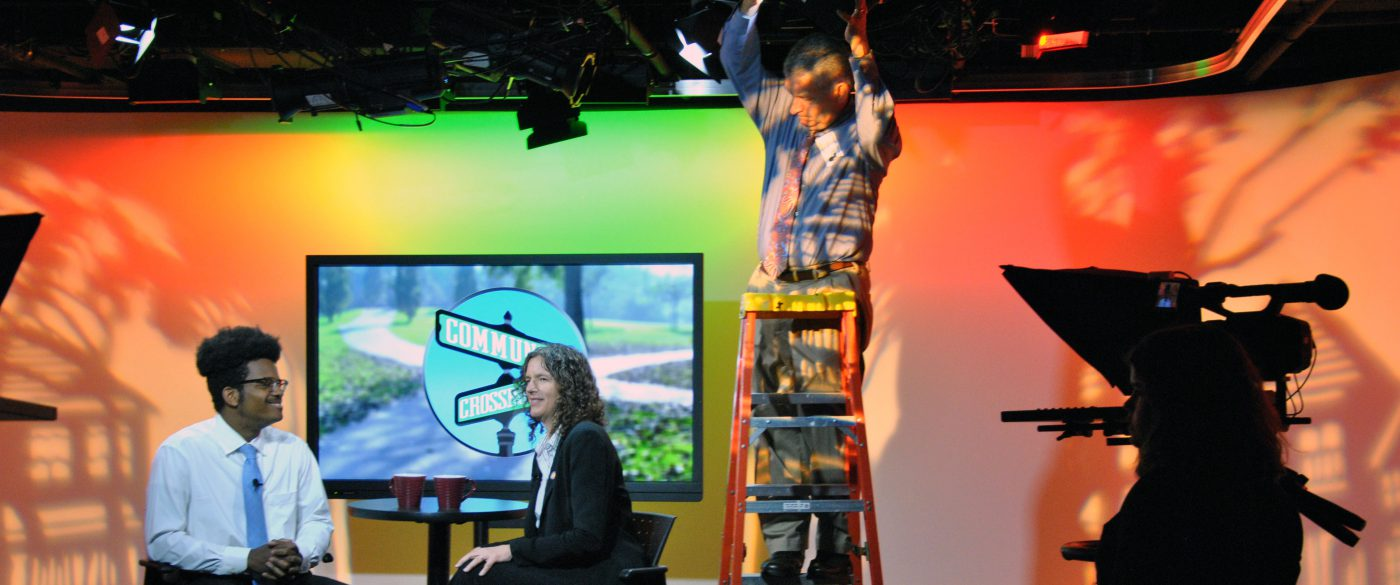Crew prepares video set for interview. Host and guest are sitting across each other with a TV screen behind them bearing the name of the show: Community Crossroads.