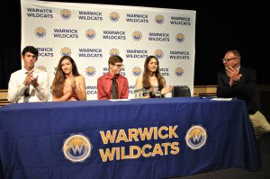 Four students sitting and athletics director sitting and applauding at a draped table with district logos. A backdrop is imprinted with Wildcats and district logos.