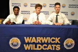 Three students sitting at draped table with district logos. A backdrop is imprinted with Wildcats and district logos.