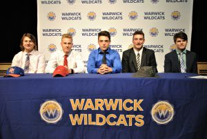 Four students sitting at draped table with district logos. A backdrop is imprinted with Wildcats and district logos.