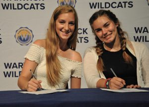 Two students sitting at draped table, signing National Letter of Intent.. A backdrop is imprinted with Wildcats and district logos