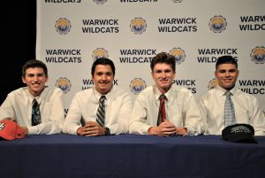 Four students sitting at draped table. A backdrop is imprinted with Wildcats and district logos