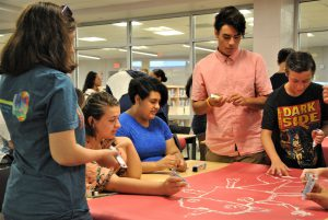 In the school's media center, a group of students sit or stand around a table. They are drawing a creature on red paper using tubes of toothpaste.on red paper.
