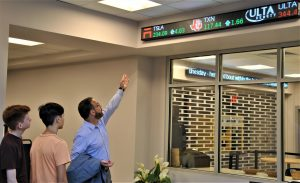 In the school's media center, and adult points two students to a marquis showing stock market updates. mation.