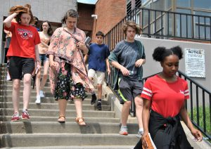 Group of students running down a flight of stairs outside a school building