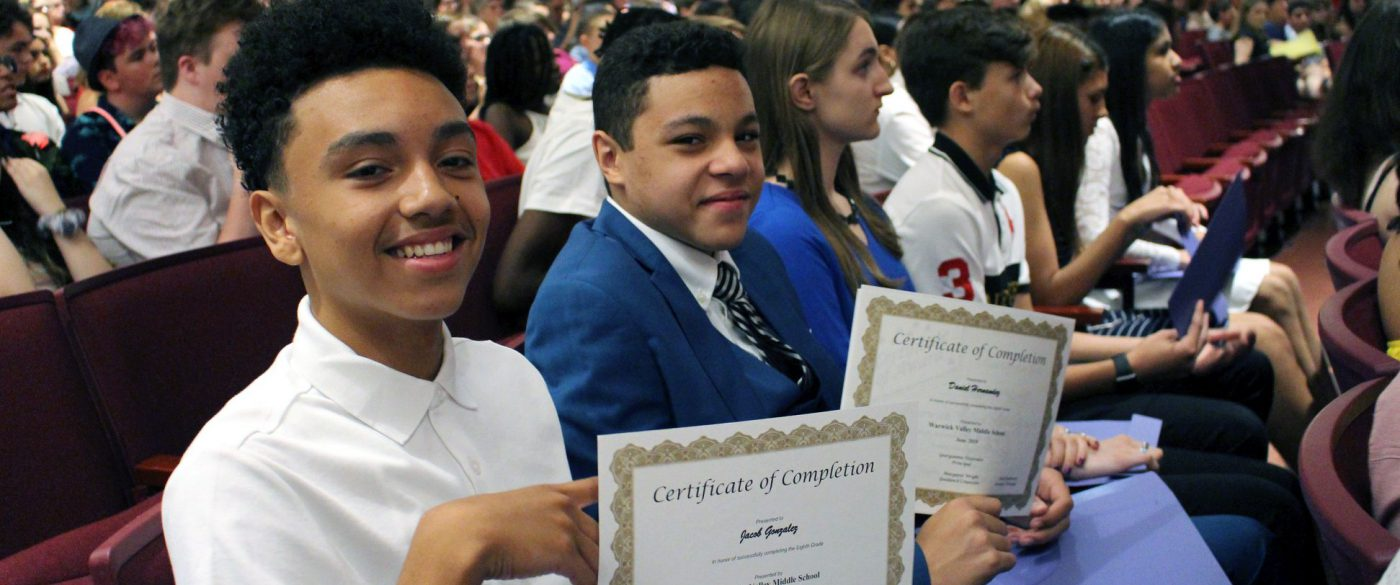 Students sit in a school auditorium holding their middle school certificates of completion.