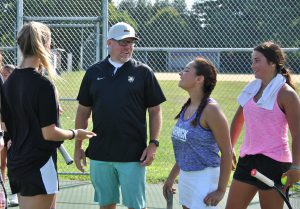 Tennis coach and three players engage in conversation on the court.