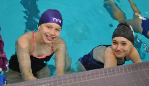 Two simmers in the pool smiling at the camera