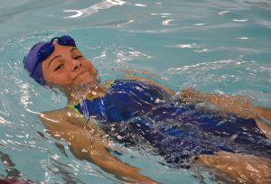 Swimmer doing back stoke and smiling at camera