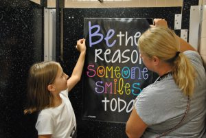 "Student and adult hang poster on bathroom door. Poster reads, ""Be the reason someone smiles today."""