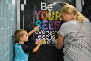 "Student and adult set poster on bathroom door. Poster reads, ""Be yourself. Everyone else is taken."""