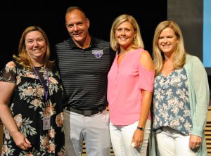 A group of teachers smile after receiving their service pins for dedication to the district.