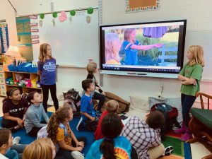 Two students stand at both sides of a smart board presenting to others who sit on a rug on the classroom floor.