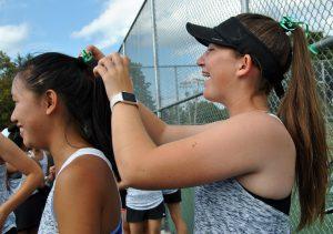 Student ties ribbon in peers' hair