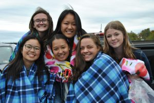 A group of girls from the tennis team  huddle together with homemade blankets wrapped around them