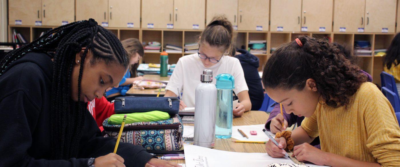 three middle school girls working at desks