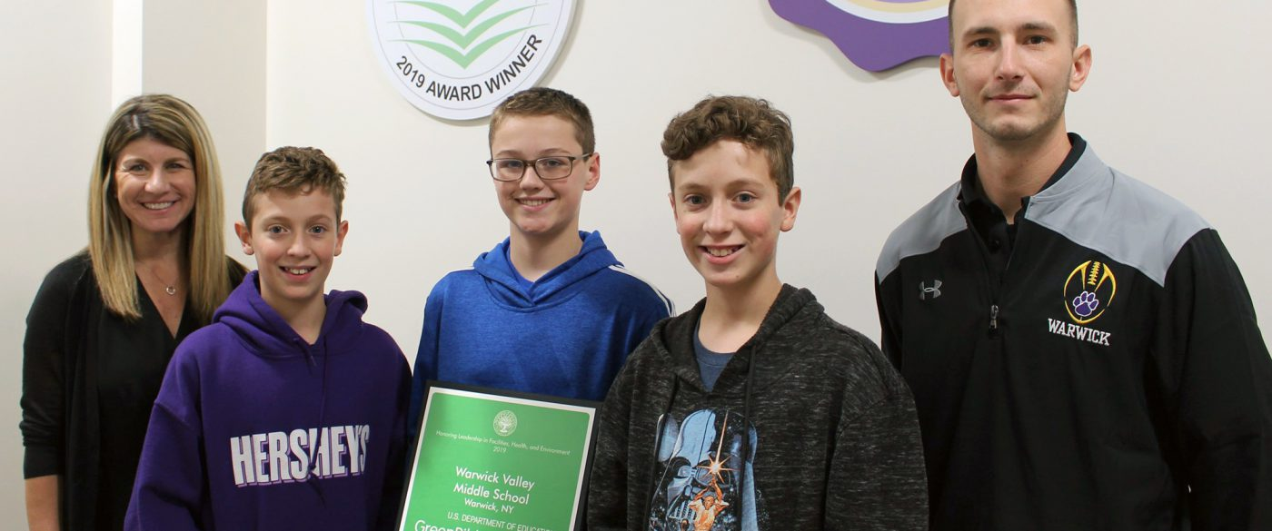 Three students and two adults pose with Green Ribbon School award.