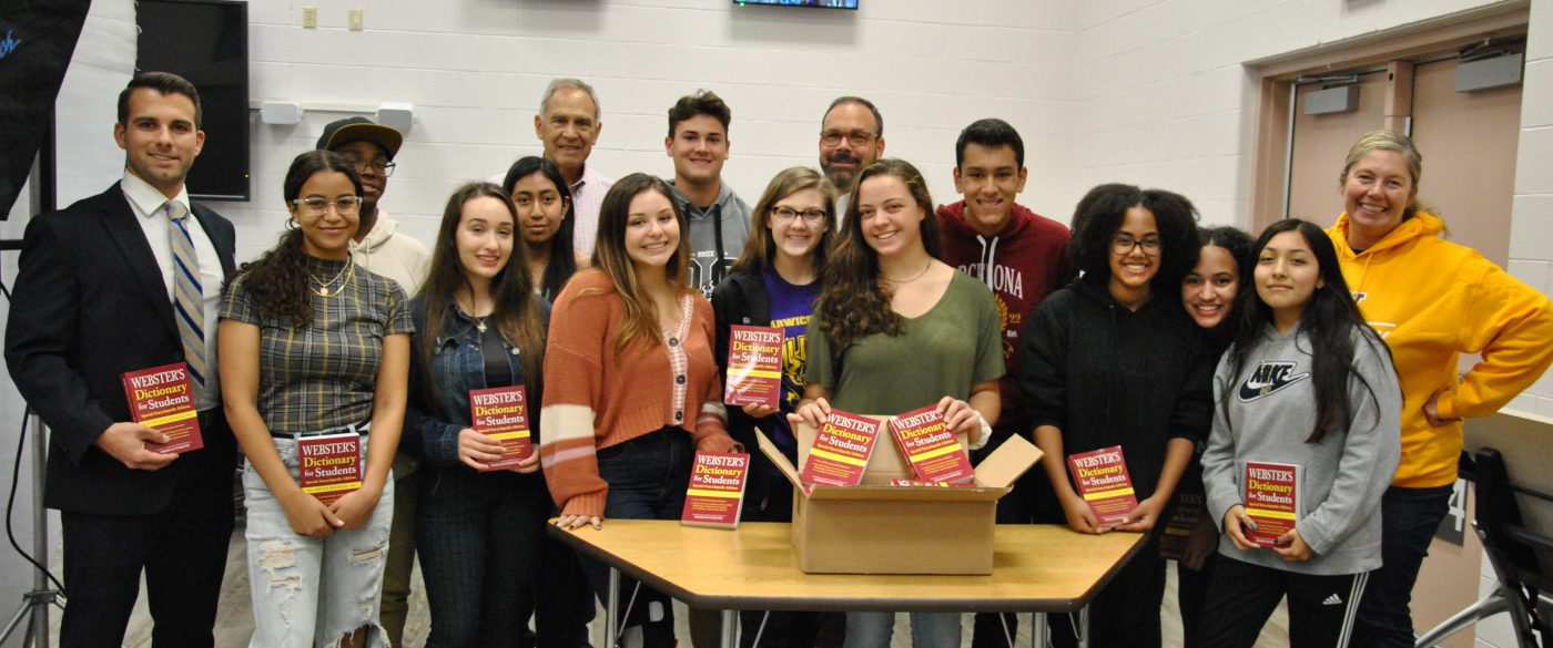 group photo of interact club holding copies of Webster Dictionary for Students