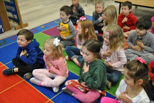 Kindergartners practicing mindfulness on the classroom floor.