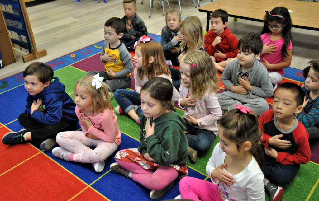 Kindergartners sit on classroom rug, eyes closed, hand over their chest, meditating.