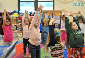 Students stretching their arms high in the classroom