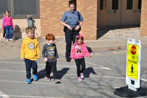 A school resource officer looks on as three kindergartners cross the street outside the school building.