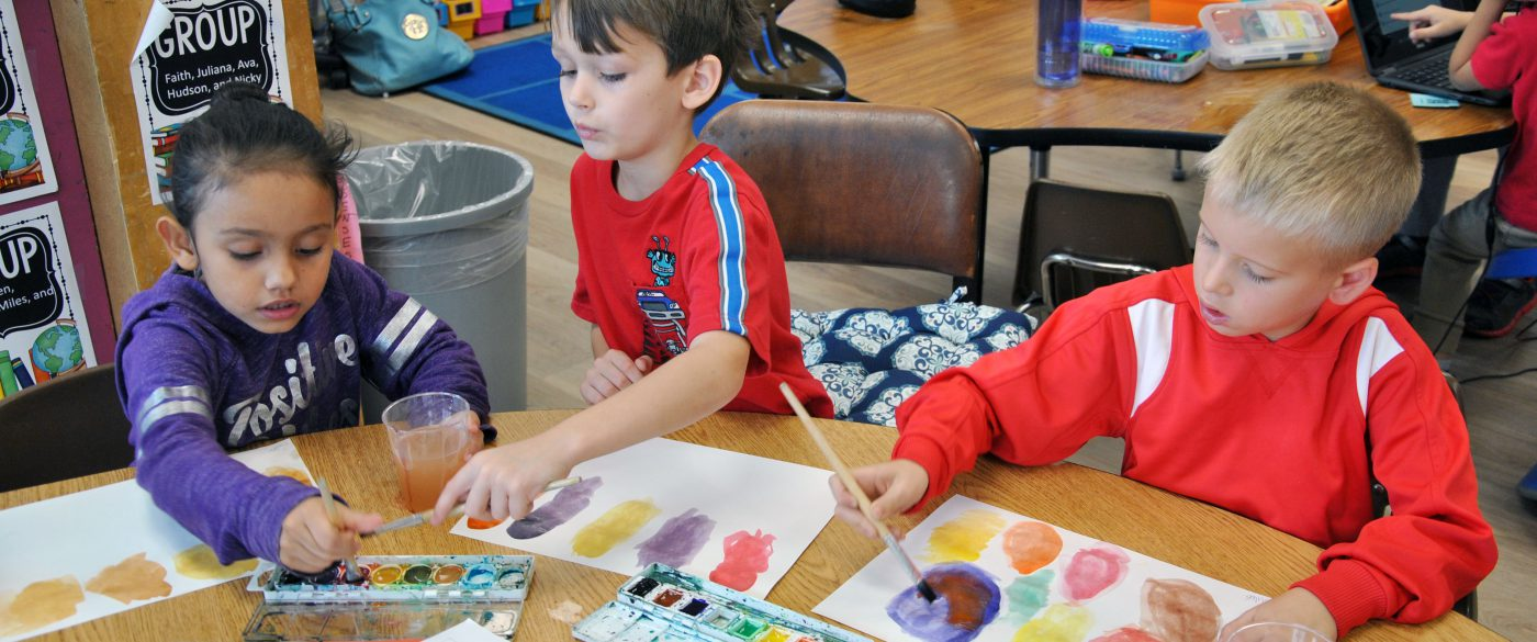 three students painting in watercolors