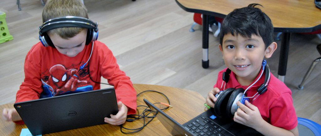 Two students working on their Chromebooks, wearing headphones.