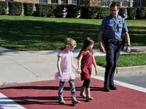 A school resource officer walks a few steps behind two students as they practice crosswalk safety.